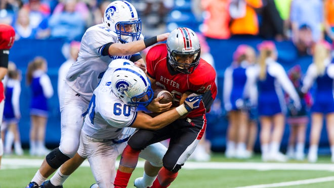 Cardinal Ritter High School senior Andre Guy (28) is gang tackled by Bishop Chatard High School sophomore David Marsh (60) and senior Isaiah West (47) during first-half action, Friday, September 19, 2014, at Lucas Oil Stadium. Bishop Chatard High School played Cardinal Ritter High School in the Class of the Titans ahead of the game between Cathedral and St. Xavier high schools.