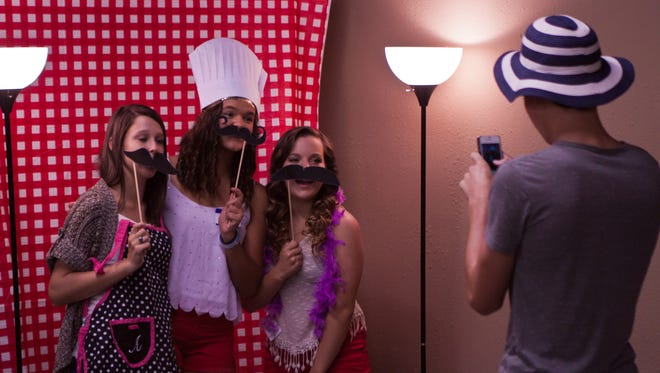 Raegan Fesmire poses with some friends in the 'selfie booth' at her going-away party. She will be spending a year in Italy as a foreign exchange student.