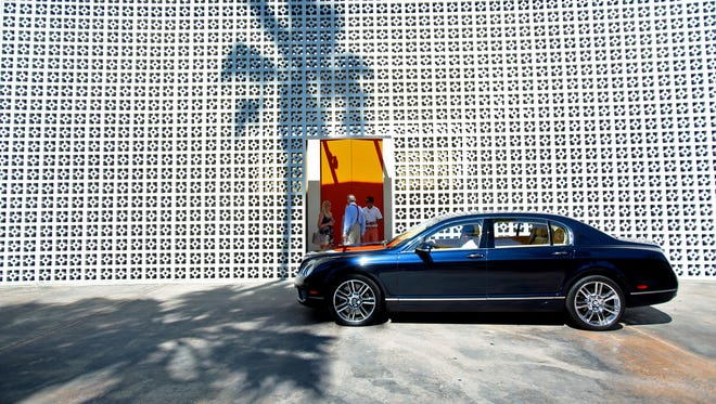 A valet pulls a car up to the entrance to the Parker Palm Springs.