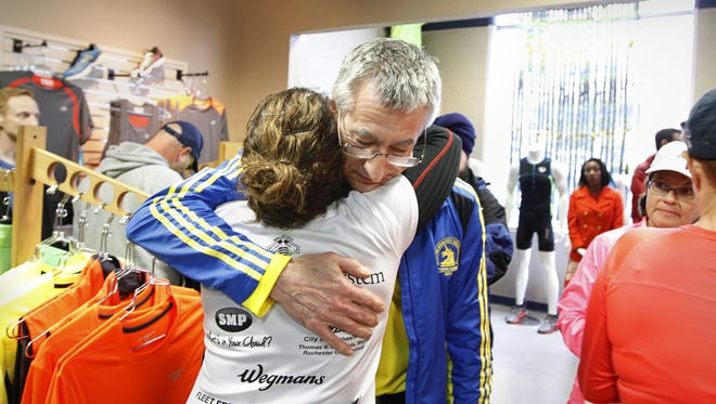 Malcolm Bugler of Henrietta is hugged by Ellen Brenner, co-owner of Fleet Feet Sports in Brighton, as he arrives at the store for a memorial run on April 16, 2013, in memory of the victims at the 2013 Boston Marathon. Bugler ran in the marathon and finished about 40 minutes before the two bombs went off at the finish line.