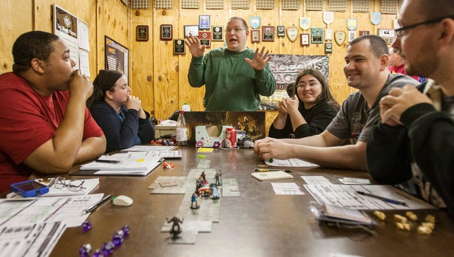 Dungeon master Aaron Heiser (center) describes a scenario to players during a game of Dungeons and Dragons at Days of Knights in Newark, Del., earlier this month.