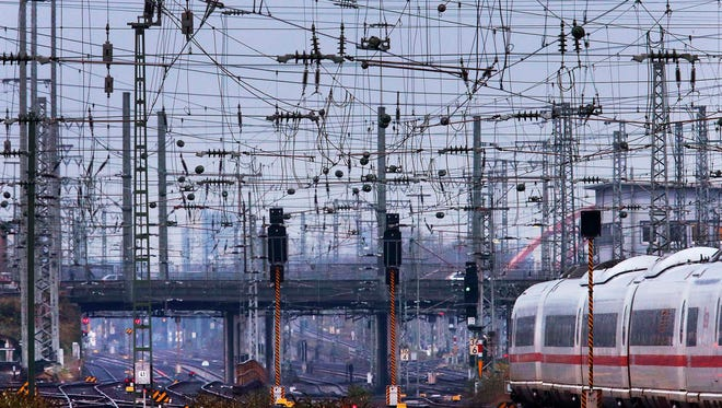 Plenty of wires hang over the rails as a train leaves the main train station in Frankfurt, Germany, Dec. 5, 2017.