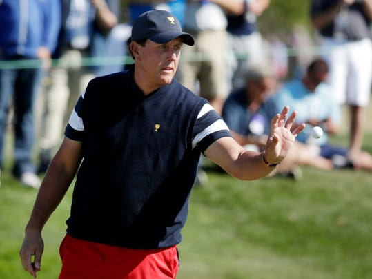 FILE - In this Sunday, Oct. 1, 2017, file photo, United States' Phil Mickelson gets his ball back after putting on the third hole during the final round of the Presidents Cup golf tournament at Liberty National Golf Club in Jersey City, N.J. Mickelson hasn't had his fill when it comes to the cup. He turns 48 next year and desperately wants to be on the Ryder Cup team, most likely his last chance to win one in Europe.  (AP Photo/Julio Cortez,File)