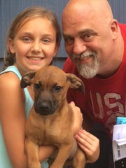 Greg Hrehorovich with his daughter, Gianna, who holds Magnus, a puppy they adopted from the Walthours.