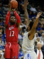 NJIT guard Anthony Tarke (12) shoots as Seton Hall guard Myles Powell (13) tries to block the shot during the first half of an NCAA college basketball game, Saturday, Nov. 18, 2017, in Newark, N.J. (AP Photo/Julio Cortez)
