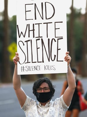 A protester holds up a sign as a group marches May 30 in Phoenix to protest the death of George Floyd.