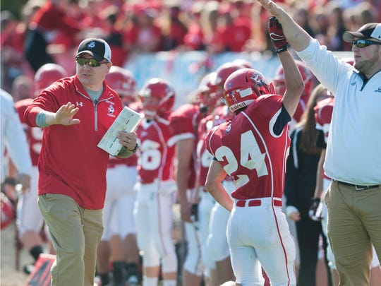 Manitowoc Lincoln's new football head coach Rick Ducat, left, gives instructions to his players during the homecoming game against Sheboygan North at Ron Rubick Field on Saturday, Oct. 10. The Ships defeated the Raiders 48-14.