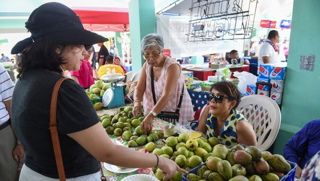 Event goers check out the mango selection during the 12th annual Agat Mango Festival on May 26, 2018.