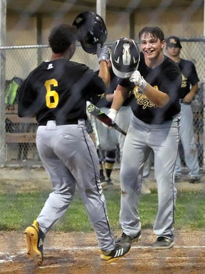 New London's Holvin Catala steps on home plate and tips his hat to Carter Allen after a solo homer, and game-winning run, in the top of the sixth inning against West Burlington Thursday at West Burlington High School.