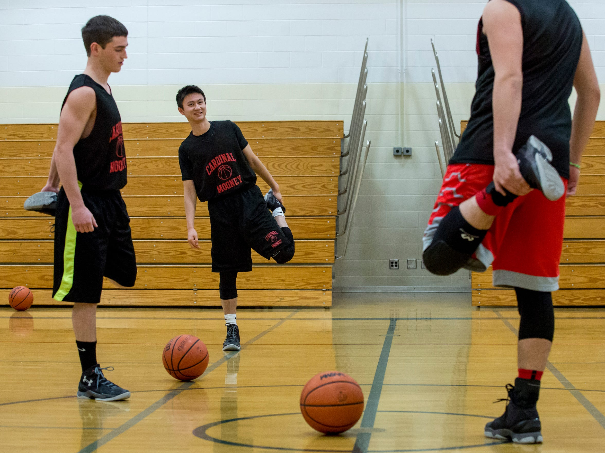 Senior Chris Xuan, 19, stretches with other members of the basketball team during practice Wednesday, Jan. 27, 2016 at Cardinal Mooney High School in Marine City. Xuan is an exchange student from Shenzhen, China.