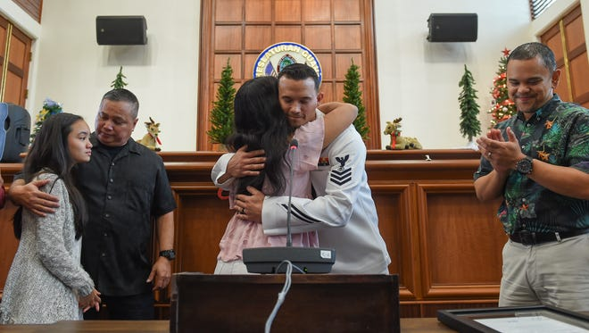 """U.S. Navy Petty Officer 1st Class Anthony """"Tony"""" Mugavero receives a hug from Cynthia Manibusan at the Guam Congress Building on Dec. 29, 2017. Manibusan was aided by Mugavero in the pursuit of a perpetrator who had snatched her purse at the Micronesia Mall on Dec. 23."""