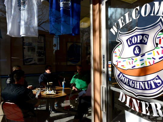 Four of the original nine founders sit at a table and enjoy coffee and breakfast at Cops and Doughnuts in Clare.