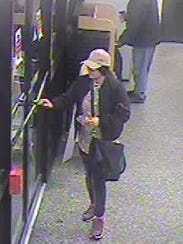 This surveillance image shows a woman who placed a skimming device in an ATM, police said.