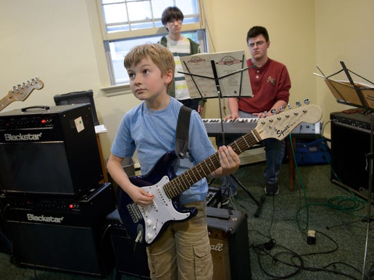 (From left) Konner Dye, 10, of Cherry Hill, Peter Rushing, 14, of Medford Lakes, and Miles Smith, 16, of Cherry Hill, rehearse music by Queen at the NJ School of Music in Cherry Hill, N.J. on Wednesday, May 11, 2016.