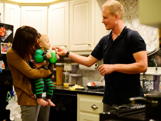 Erin Doemland holds her son, Sammy as her husband Chris feeds him a piece of apple. Chris does most of the cooking, so when he started eating healthier it helped the whole family eat healthier.