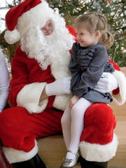 Elizabeth Gigot, 2, of Wauwatosa, shares her holiday wish list with Santa Claus at the Milwaukee County Zoo's Breakfast with Santa.