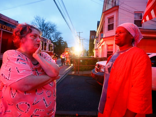 Residents Florence Konwickie, l, and Cassandra Johnson talks as firefighters are at the scene of an early morning 3-alarm fire on Speedwell Avenue in Morristown. October 9, 2017. Morristown, New Jersey