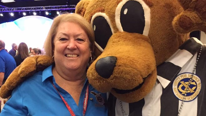 Nancy Golnick poses with Time Out Teddy, the mascot used by the National Exchange Club to help children in crisis.
