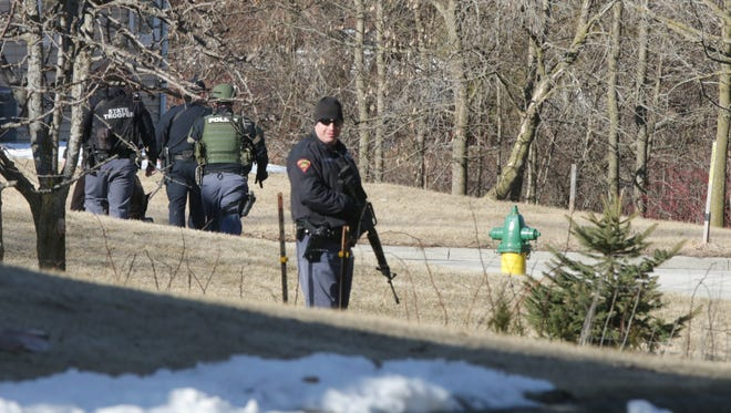 Armed police patrol backyards near a street at Kiel High School following reports of shots fired, Friday, March 23, 2018, in Kiel, Wis. Kiel High School cancelled classes after shots were heard by a staff member at the high school before classes started at Kiel.