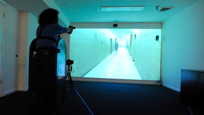 USA TODAY reporter Marisol Bello aims at a shooter in a police action simulator at the Law Enforcement Legal Defense Fund headquarters.