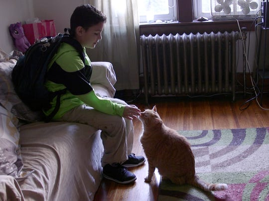 Ezekiel Melendez pets the family cat in the small apartment he shares with his mother and older brother.