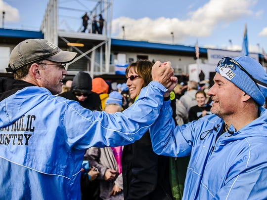 Lansing Catholic Head Cross Country Coach Tim Simpson ,left, celebrates with Michael Markey, the father of LCC runner Ethan Markey, after Lansing Catholic won the team championship Saturday November 7, 2015 at Michigan International Speedway in Brooklyn. KEVIN W. FOWLER PHOTO