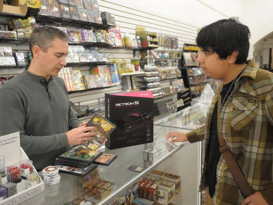 C.B. Thompson, left, talks with Noe Anguiano about Hyperkin's new RetroN5, and about Anguiano's trade-in for games at GameQore, 107 E. Main St. in downtown Visalia. The RetroN5 is a retro gaming console that supports games from a variety of classic game systems in high definition. GameQore is offering a sale of 20 percent off pre-owned board games, pre-owned role playing games, pre-owned manga and pre-owned graphic comics Black Friday through Sunday.