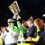 Kyle Busch hoists the Sprint Cup championship trophy after winning the Ford EcoBoost 400 at Homestead-Miami Speedway.