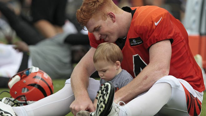 Cincinnati Bengals quarterback Andy Dalton (14) stretch with his son Noah, 13 months, on the field after practice at the Bengals training facility next to Paul Brown Stadium in downtown Cincinnati on Monday, Aug. 17, 2015.