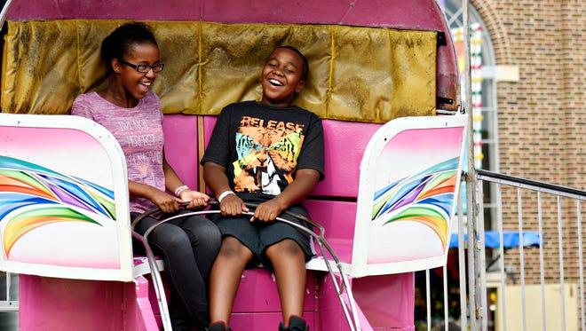 Cousins Virginia Ball, 14, left, and Kabari Hinton, 10, both of Dallastown, ride the Tilt-a-Whirl at the York Fair in York, Sunday, Sept. 18, 2016. Dawn J. Sagert photo