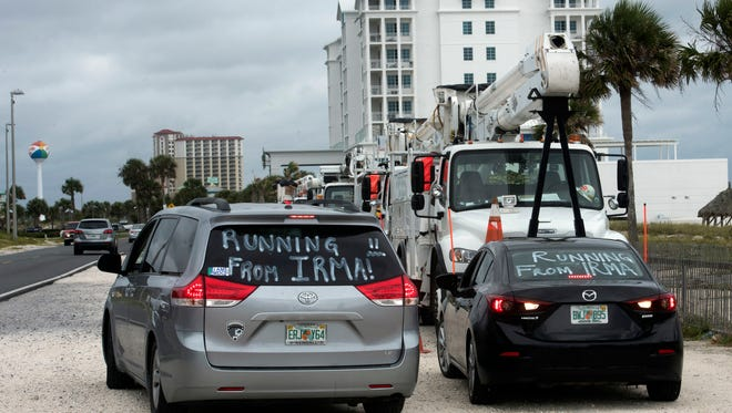 """Vehicles with """"Running from Irma!"""" painted on their windows are parked on Monday, Sept. 11, 2017, at Pensacola Beach,"""