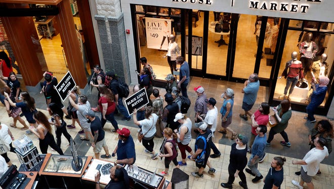 Protesters march through West County Mall on Saturday, Sept. 16, 2017, in Des Peres, Mo.