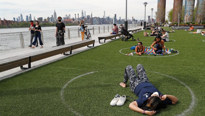 People relax in circles marked on the grass for proper social distancing at Brooklyn's Domino Park, Monday, May 18, 2020, in New York, during the current coronavirus outbreak. The circles were added after the park, which has excellent views of the Manhattan skyline, became severely overcrowded during a spate of warm weather just over a week ago.