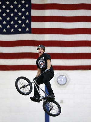 """Andrew Fox, with AGA Nation, performs a trick April 13 during the """"Bring Your 'A' Game to School"""" BMX event at Menasha High School. The event was brought to the school through the National Guard. To see a photo gallery of the event, go to postcrescent.com."""