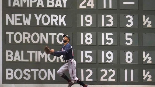 Atlanta Braves left fielder Nick Markakis tries to chase down a deep ball in front of the scoreboard on the Green Monster at Fenway Park. The Red Sox, who close out a three-game series with the Braves on Wednesday, remain in last place in the AL East.