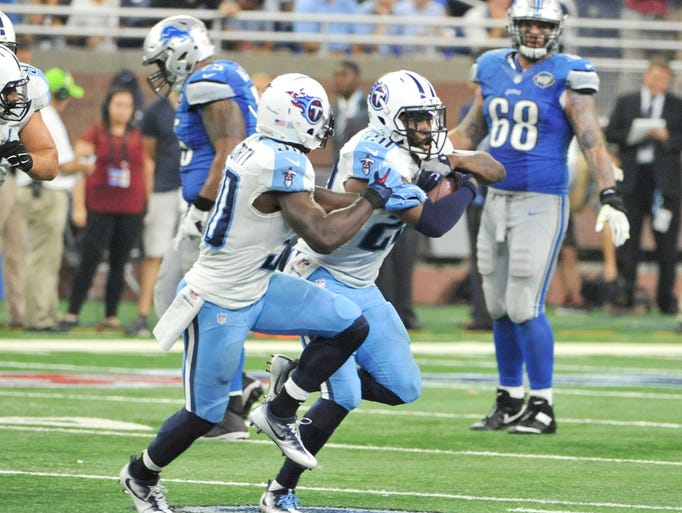 Titans' Perrish Cox, center, runs with the ball after