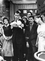 """Television disc jockey and """"American Bandstand"""" host Dick Clark is seen surrounded by teenage fans in 1957 during a broadcast."""
