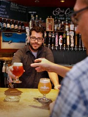 Ben Bourgeois, bartender at Stubby's Gastrogrub & Beer Bar, serves a pint of Clutch Cargo IPA from Lakefront Brewery.
