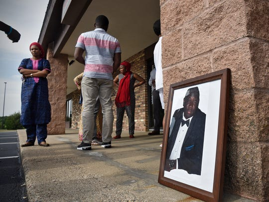 A photograph of Keletigui Keita reminds friends and family members of his memory Friday, June 9, during a vigil outside a shop Keita used to co-own in St. Cloud.