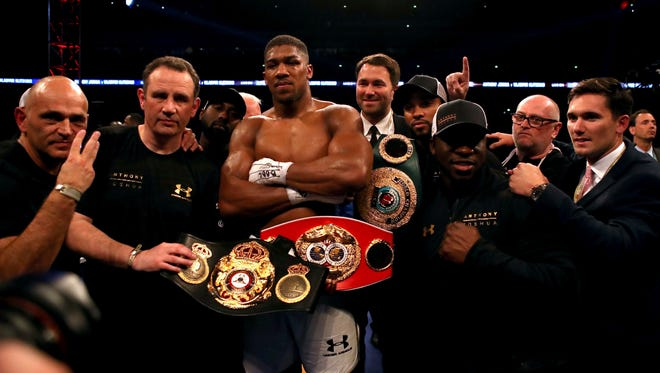 Anthony Joshua shows off his championship belts after beating Wladimir Klitschko on Saturday.