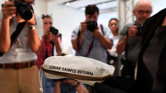 This file photo from July 13 shows Sothebys Cassandra Hatton as she displays the Apollo 11 Contingency Lunar Sample Return Bag, used by Neil Armstrong on Apollo 11 to bring back the very first pieces of the moon ever collected, during a media preview for Space Exploration auction in New York.