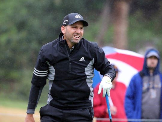 Sergio Garcia stands on the first green in the rain