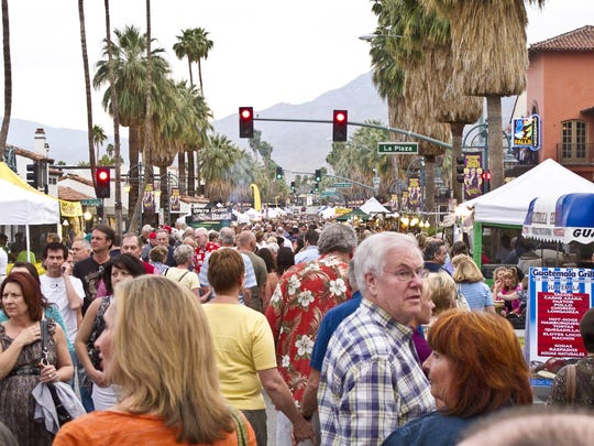 A large crowd wanders Palm Canyon Drive for the Palm Springs VillageFest in downtown.