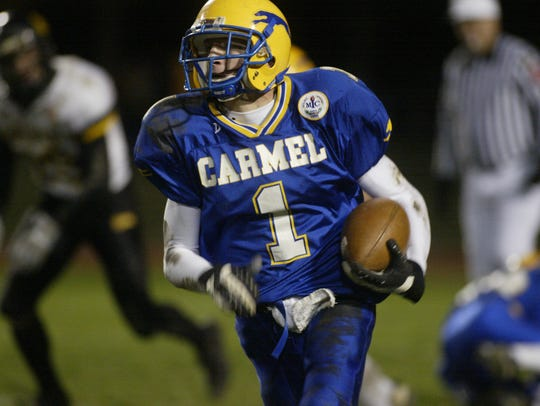 Carmel's Collin Taylor returns a kickoff during a 2004