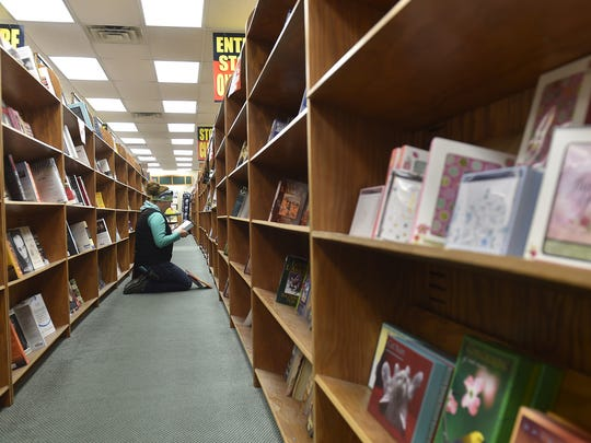 Mariah Sixel of Nasawaupee selects books from Book World, 30 N. Third Ave., Sturgeon Bay. The store plans to close in mid January.