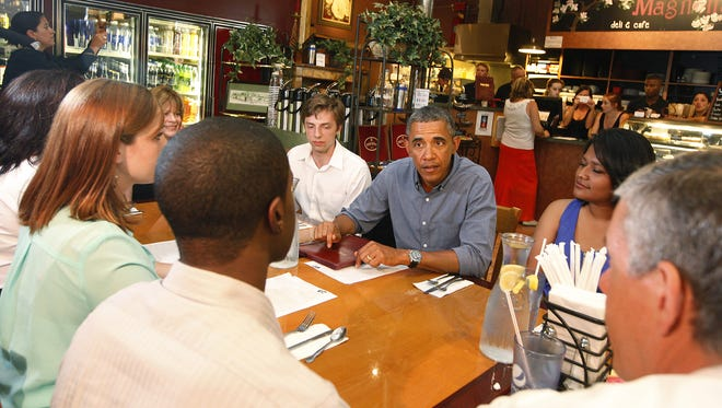 President Barack Obama talks to a table of patrons inside Magnolia's.