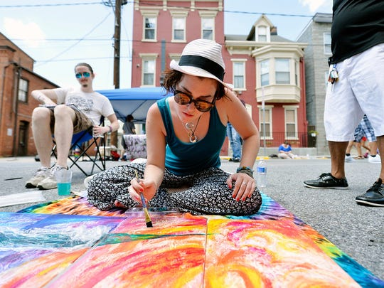 """Faith Reisinger of Carlisle works on a painting for The Parliament Arts Organization during Equality Fest Sunday, Aug. 2, 2015. The second annual Equality Fest, held in the 100 block of East King Street in York, featured a vow renewal ceremony and a wedding expo in the Bond Building, as well as music, crafts, food and games. The festival, which was inspired last year by the legalization of gay marriage in Pennsylvania, is designed to celebrate the diversity of Pennsylvania and York residents."
