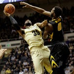Gabe Olaseni, right, tries to affect the shot of Purdue guard Rapheal Davis. Olaseni finished with nine points and 16 rebounds in Iowa's 67-73 loss.