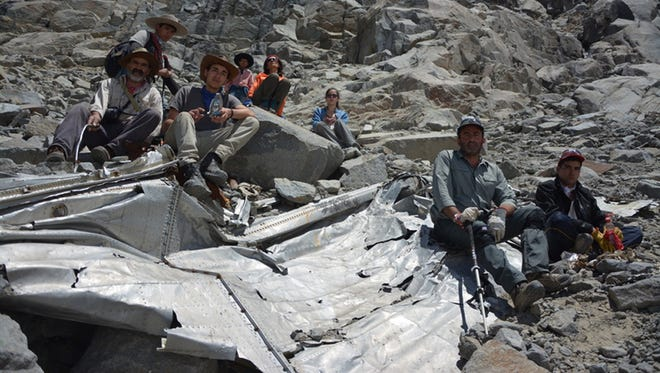 In this Jan. 26, 2015 photo provided by Leonardo Albornoz, a group of Chilean mountaineers pose for a photo on what they say is the wreckage of a plane that crashed in the Andes 54 years ago, killing 24 people, including eight members of a professional soccer team.