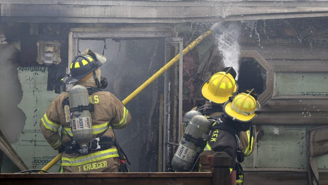 Firefighters work Monday to put out a house fire in Black Creek along State Road.